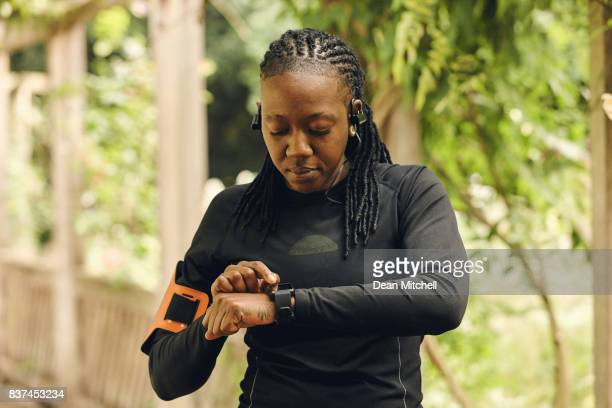 African woman setting fitness app before workout