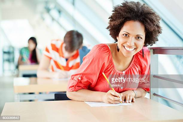 African woman sitting at an exam in college