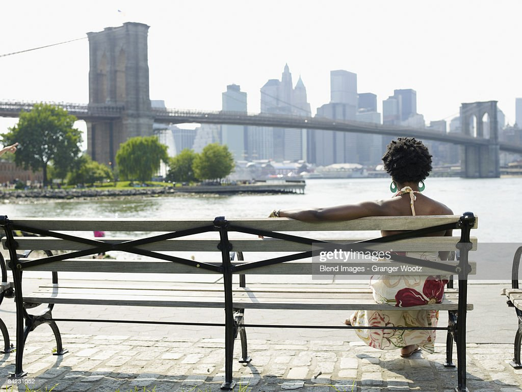 African woman sitting on bench at urban waterfront : Stock Photo