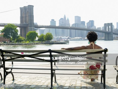 African woman sitting on bench at urban waterfront