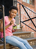 African woman sitting on steps eating salad