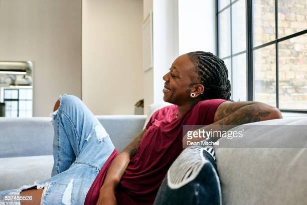 African woman sitting relaxed on sofa at home
