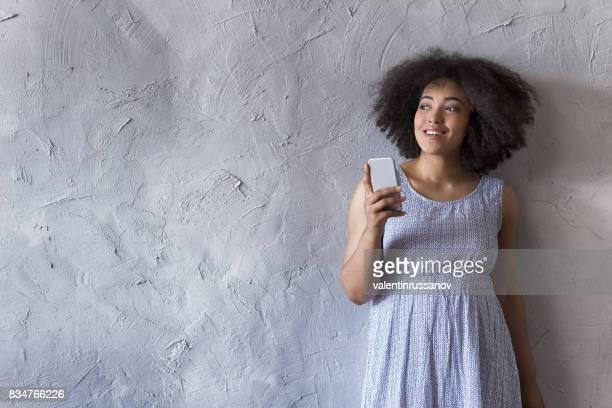 African woman social networking in front of gray wall