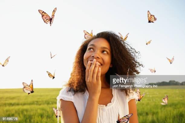 African woman standing among butterflies in meadow