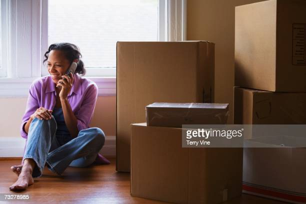African woman using cell phone on floor next to moving boxes