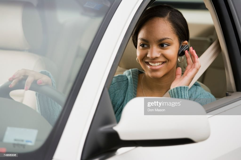 African woman using hands free device in car : Stock Photo