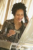 African woman using telephone and holding credit card