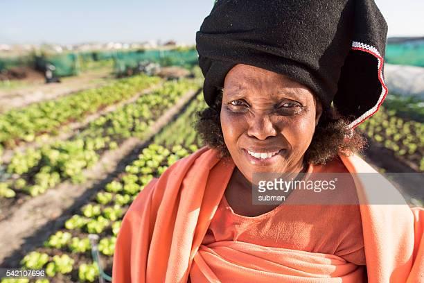 Afrikanische Frau zu Fuß mit ernte durch den Garten