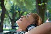 African woman wearing headphones in park