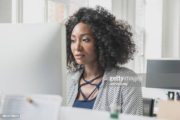 African woman with curly Afro hair using computer and concentrating