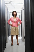 African woman with hands on hips in computer server room