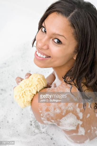 African woman with sponge in soapy water