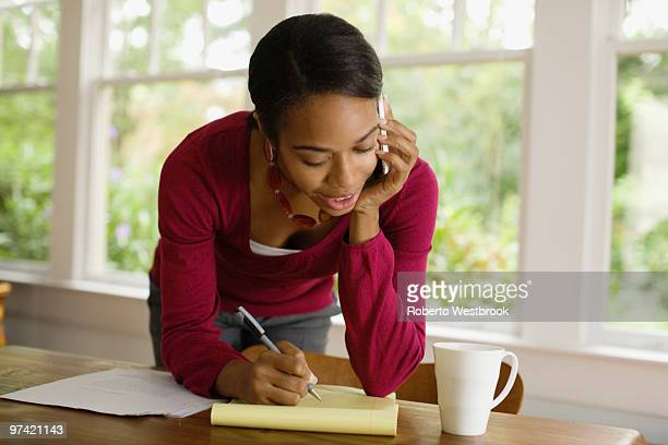 African woman writing and talking on cell phone