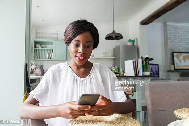 African women at home sending a text message.