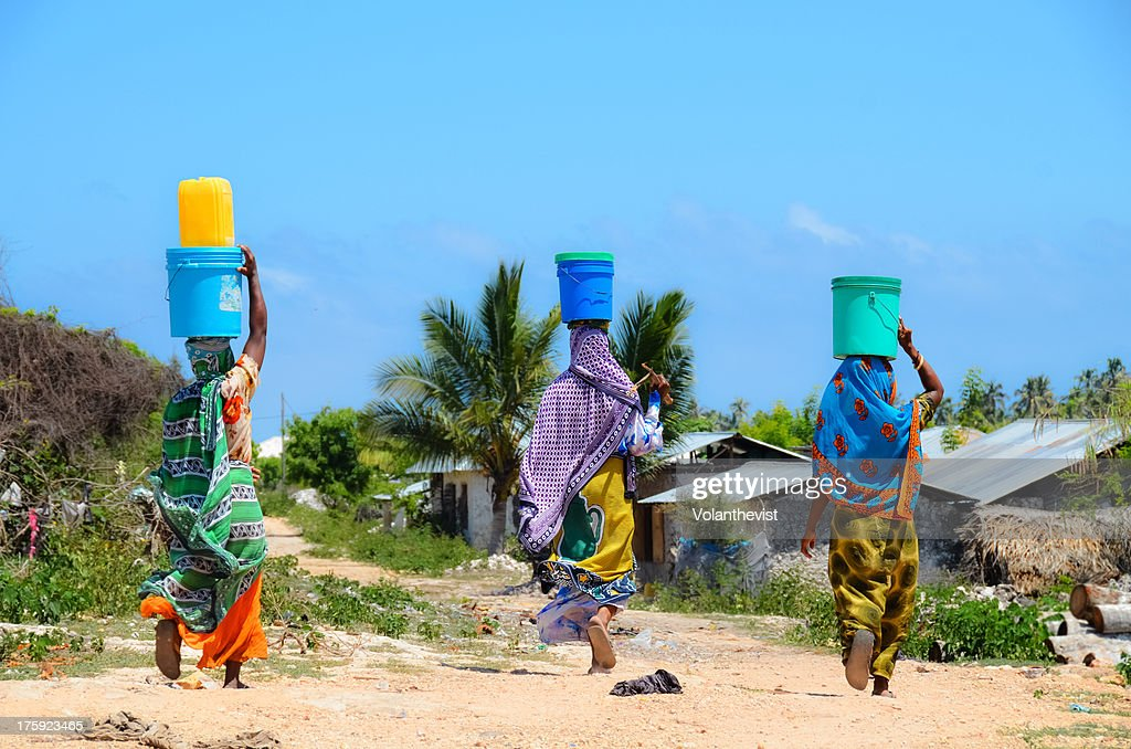 African women go to fetch water w/ buckets on head