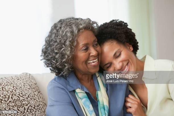 African women hugging on sofa