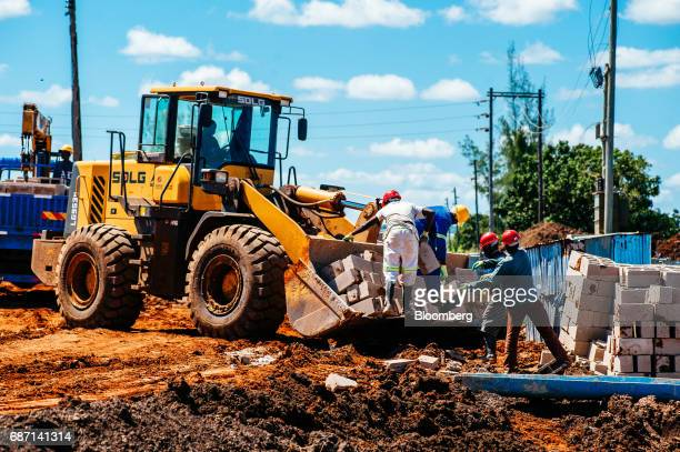 African workers load building blocks onto the bucket of a frontloader at the construction site for a hydro pumping station which will supply water...