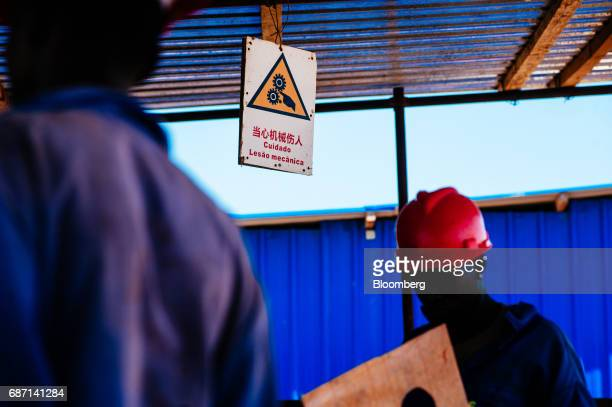 African workers stand beneath a work safety sign at the construction site for a hydro pumping station which will supply water from the Limpopo river...