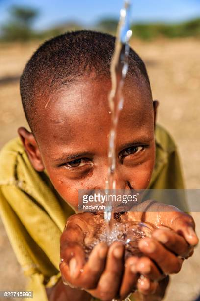 African young boy drinking fresh water on savanna, East Africa