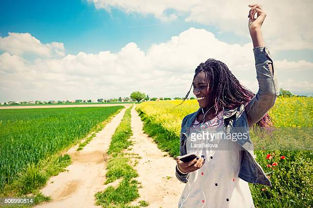 Afrique jeune femme écoutant de la musique dans campagnes qui l'entourent
