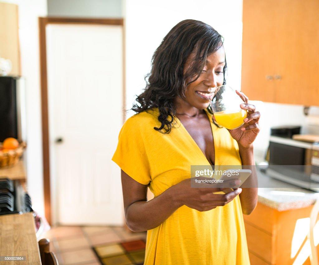 Afrikanische lächelnde junge Frau trinkt Orangensaft : Stock-Foto