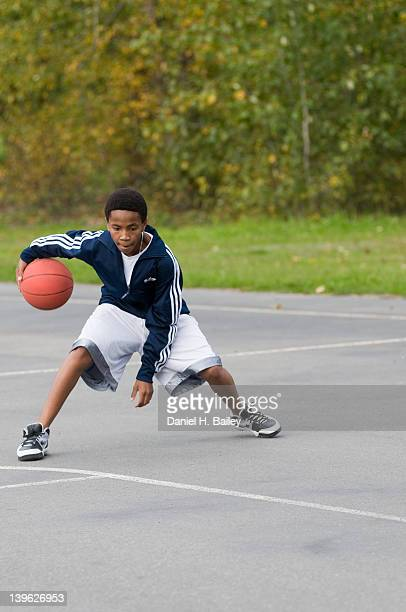 AfricanAmerican 13 year old teen playing basketball by himself on an outside court at a park