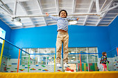 Full length low angle portrait of happy African-American boy jumping on trampoline in colorful kids play center, copy space