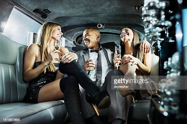 African-American businessman with young women in a limousine.