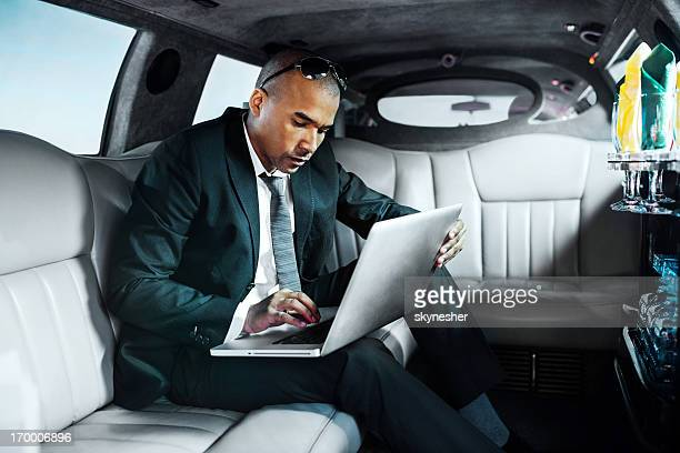 African-American businessman working on laptop in limousine.