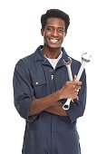 Young African-American car mechanic with wrench isolated white background.