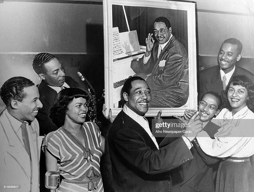 African-American composer, pianist, bandleader and Jazz musician Duke Ellington, with painting of himself, smiling, August 21, 1948.