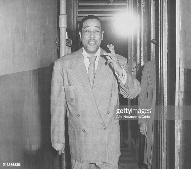 AfricanAmerican composer pianist bandleader and Jazz musician Duke Ellington smoking cigarettes in a backstage area during a concert 1960