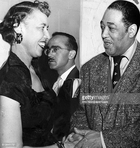 AfricanAmerican composer pianist bandleader and Jazz musician Duke Ellington and members of the National Council of Negro Women shaking hands at...