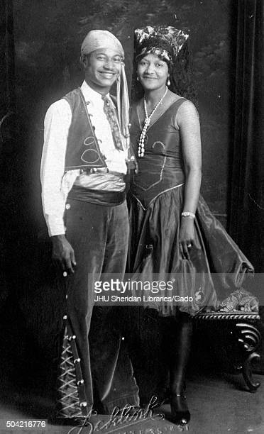 AfricanAmerican couple a man and woman smiling and posing for a portrait in a studio wearing pirate style costumes 1925