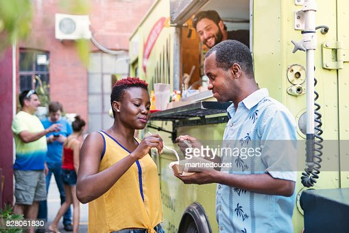 African-american couple enjoying their lunch from food truck in city street. : Stock Photo