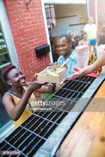 African-american couple taking out lunch from food truck. : Stock Photo