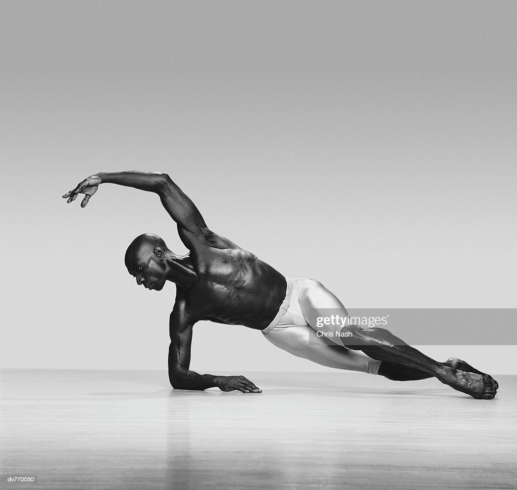 African-American Dancer Supporting Himself on the Floor by His Arm : Stock Photo