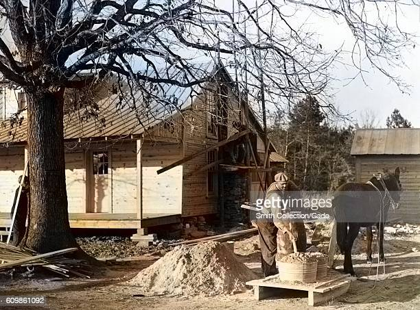 AfricanAmerican Farm Security Administration rehabilitation client mixing cement to be used in construction of his new home Raleigh North Carolina...