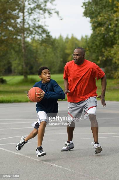 AfricanAmerican father and 13 year old teen son playing basketball together on an outside court at a park