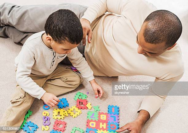 African-American father and son playing with puzzles.