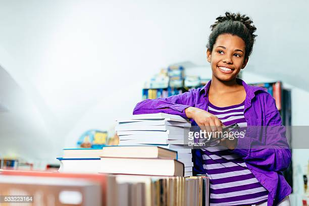 African-American high school girl on pile of books in library