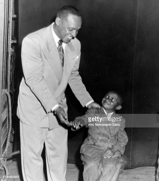 AfricanAmerican jazz vibraphonist pianist percussionist bandleader and actor Lionel Hampton and a young boy shaking hands October 30 1945
