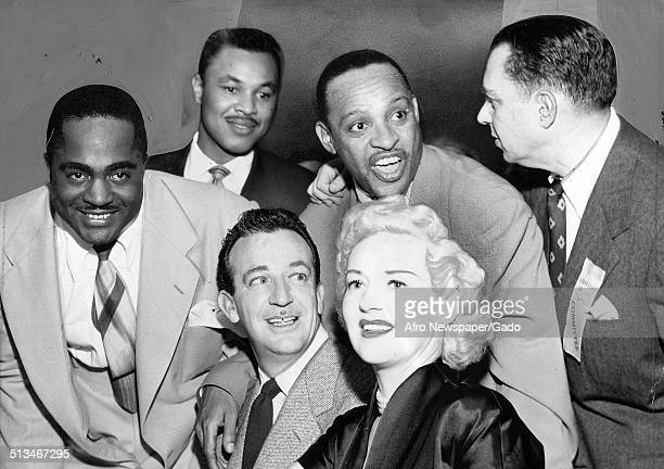AfricanAmerican jazz vibraphonist pianist percussionist bandleader and actor Lionel Hampton movie star Betty Grable and Jimmy Witherspoon conversing...