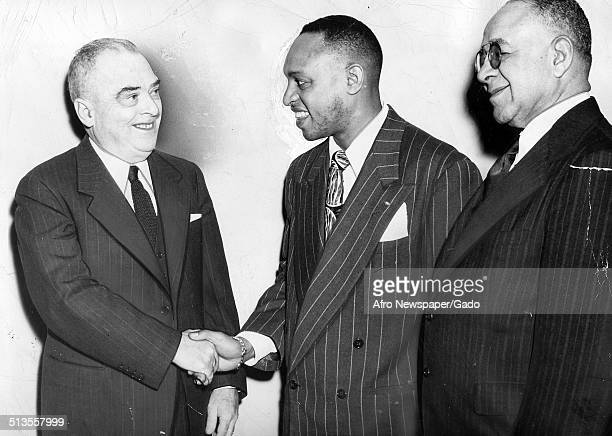 AfricanAmerican jazz vibraphonist pianist percussionist bandleader and actor Lionel Hampton Bernard Samuel and Robert J Nelson shaking hands...