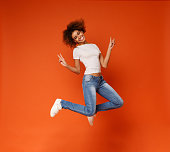 Millennial african-american girl jumping and showing peace sign, enjoy being in air, on orange background