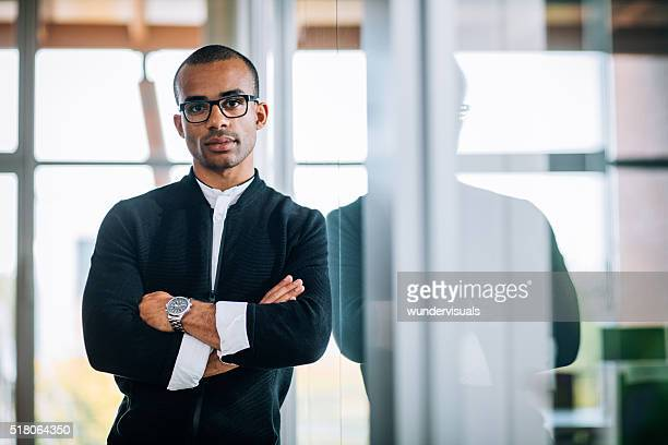 African-american leaning against office window