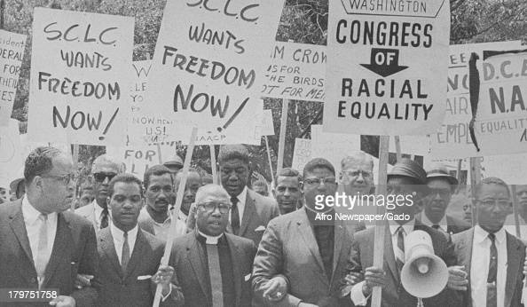 AfricanAmerican males in suits or clerical garb with picket signs protest racial inequality 1968
