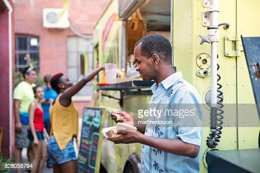 African-american man enjoying lunch from food truck in city street. : Stock Photo