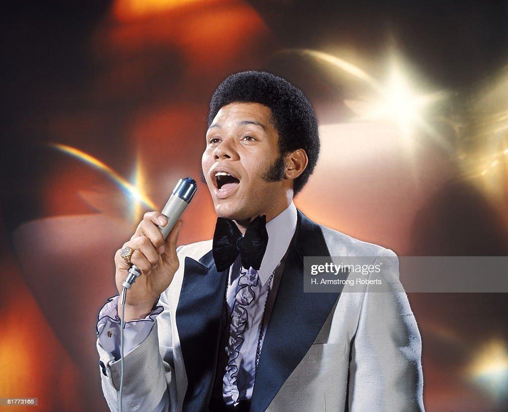 African-American Man Singing Velvet Collar Tuxedo Fashion Long Sideburns Holding Microphone Singer. : Stock Photo
