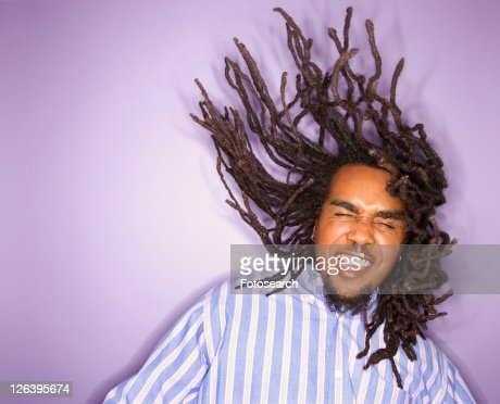 African-American mid-adult man on purple background with his dreadlocks in motion.